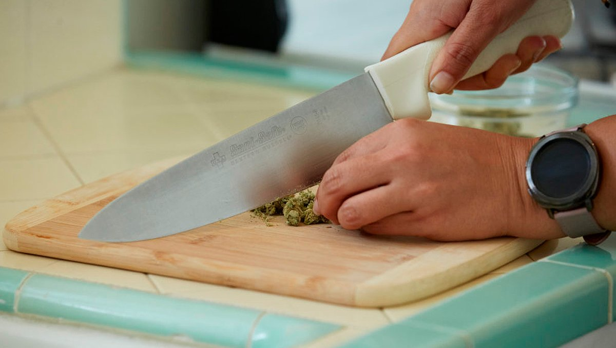 Chopping cannabis with a knife to grind it